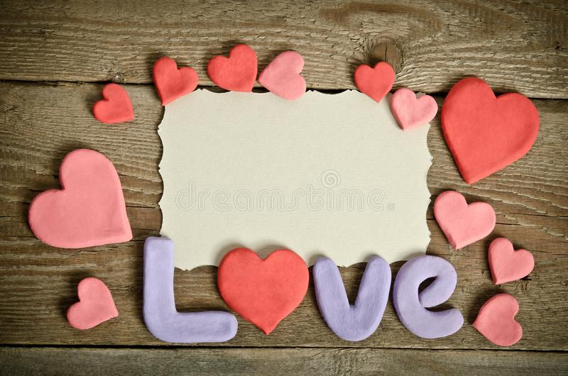 Word Love composition on the wooden board surface and many hearts royalty free stock photo