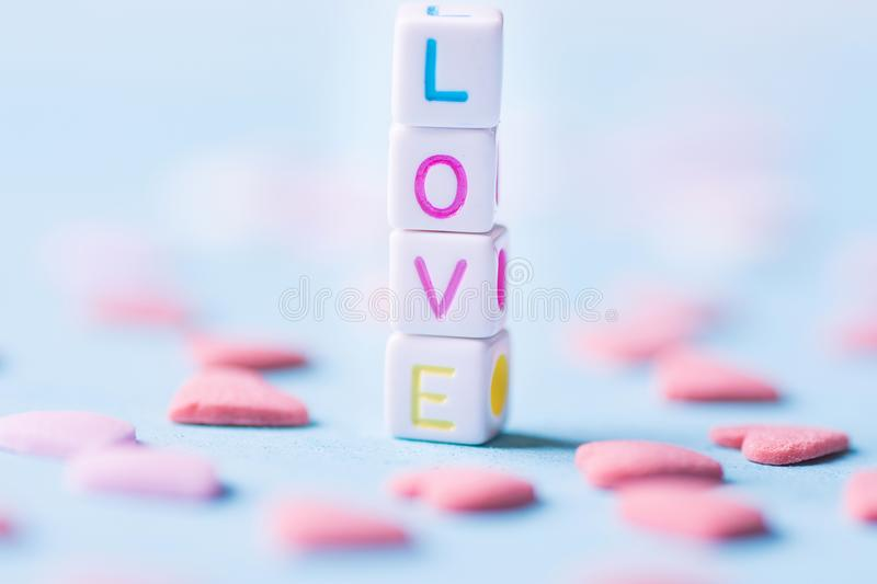 Word Love Constructed from Stacked Letter Cubes. Pink Sugar Candy Sprinkles Scattered on Light Blue Background. Romance Valentine royalty free stock photography