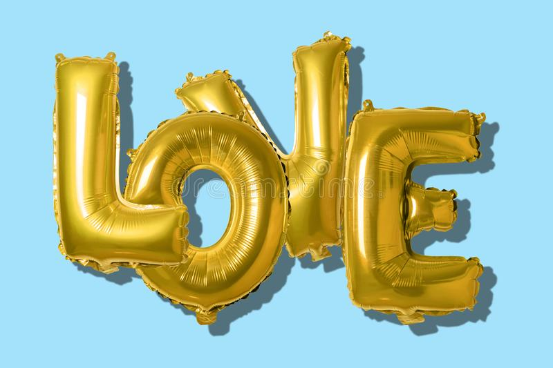 Word love in english alphabet from gold balloons on a bright background. Minimal love concept.  stock image