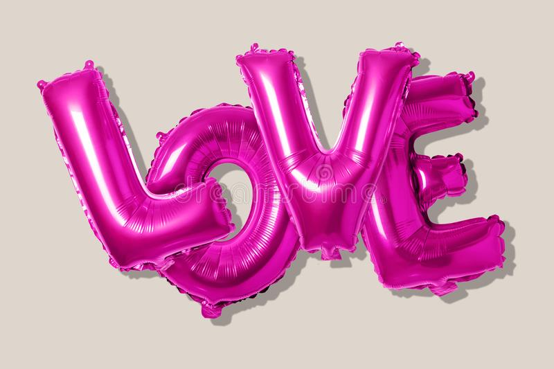 Word love in english alphabet from pink balloons on a bright background. Minimal love concept.  royalty free stock photo