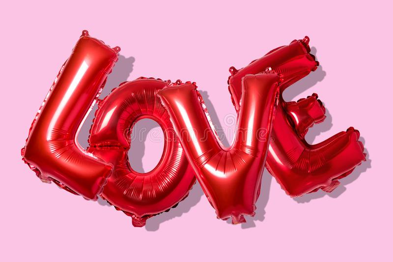 Word love in english alphabet from red balloons on a bright background. Minimal love concept.  stock photography