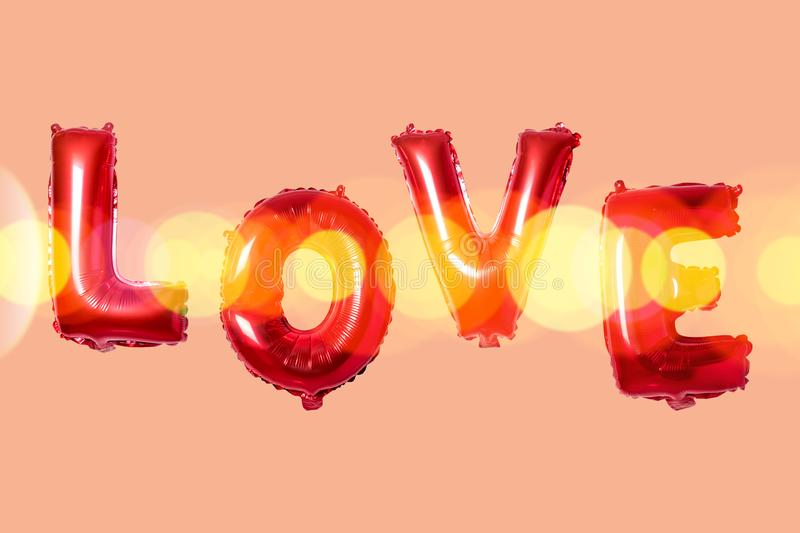 Word love in english alphabet from red balloons on a bright background. Minimal love concept.  stock photos