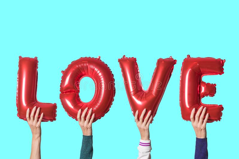 Word love in english alphabet from red balloons in hands on a bright background. Minimal love concept.  stock photo