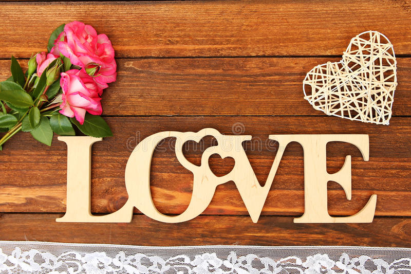 The word love and a heart with roses. On Valentine's Day stock photography