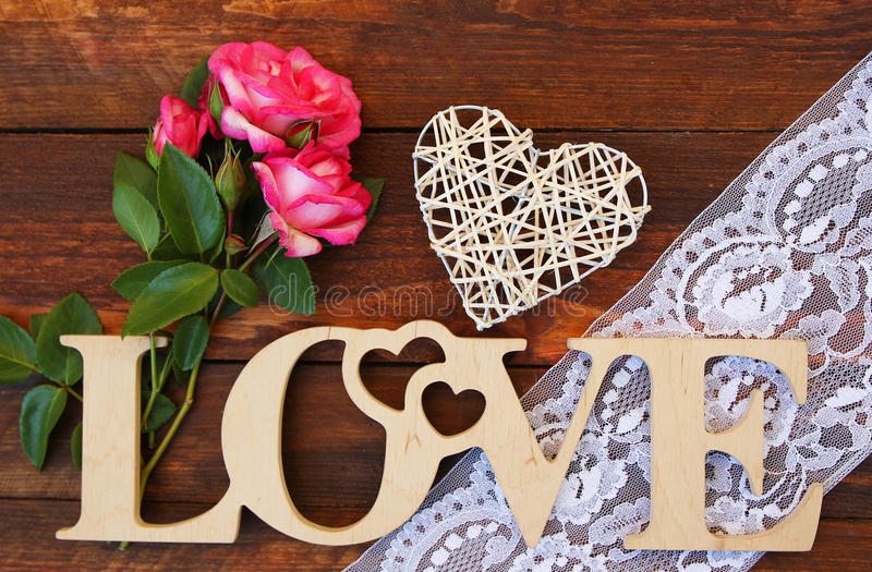 The word love and a heart with roses. On Valentine's Day royalty free stock images