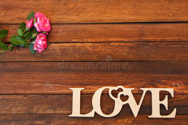 The word love and a heart with roses. On Valentine's Day stock image