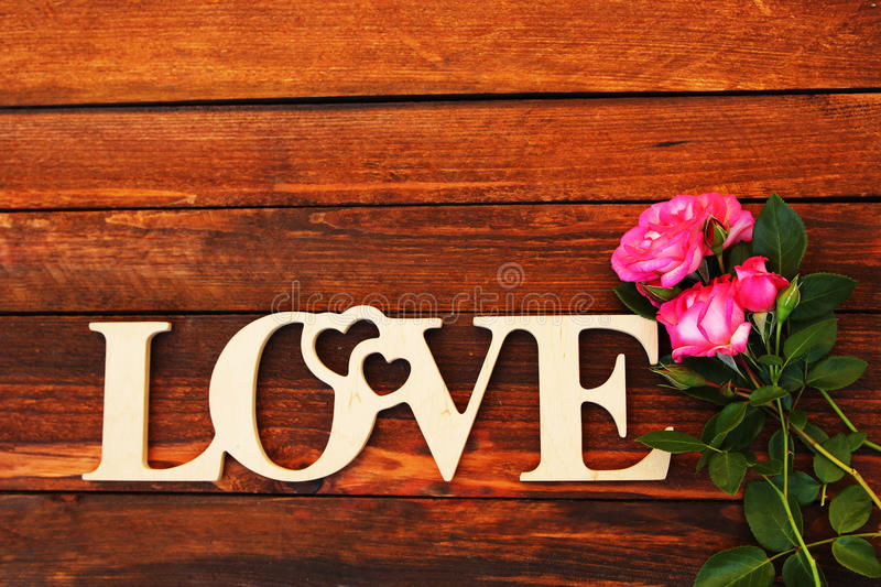 The word love and a heart with roses. On Valentine`s Day royalty free stock images