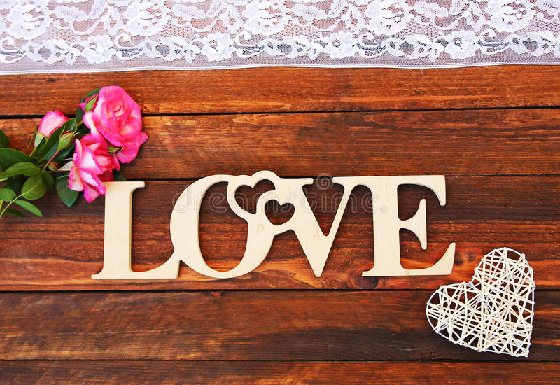 The word love and a heart with roses. On Valentine`s Day royalty free stock photo