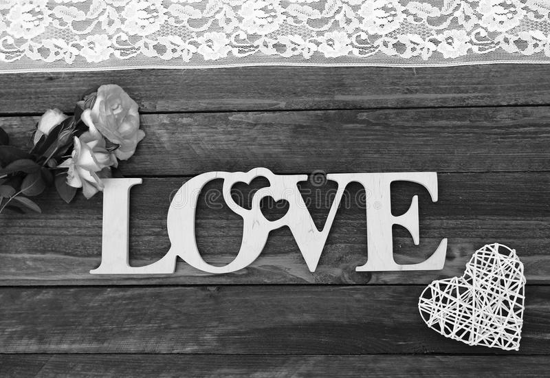 The word love and a heart with roses. On Valentine`s Day royalty free stock photography