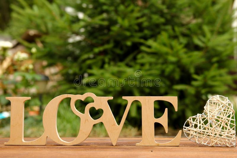 The word love and a heart with roses. On Valentine`s Day stock image