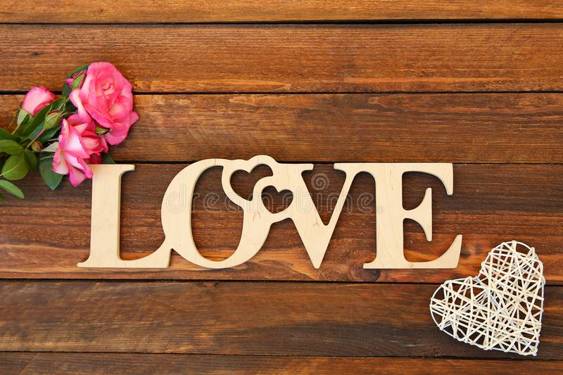 The word love and a heart with roses. On Valentine`s Day royalty free stock image