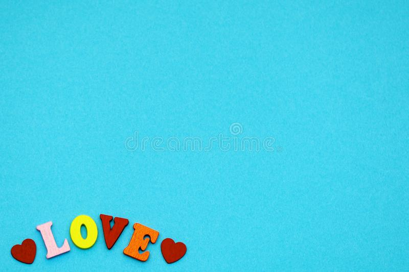 The word love and hearts on a blue background, the symbols of the holiday Valentine`s day. copy space stock image