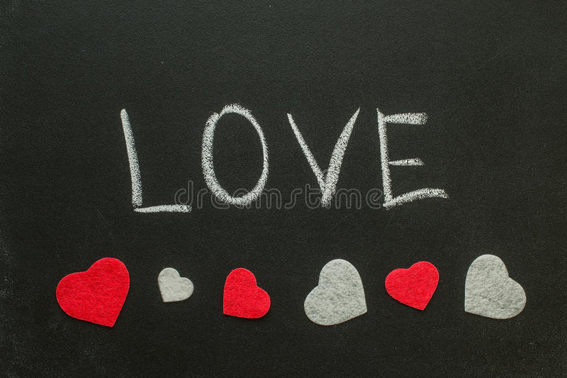The word love with hearts on the chalkboard. Valentine`s Day Concept royalty free stock images