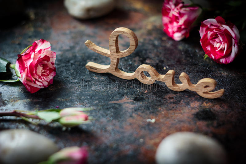 Word LOVE, hearts and flowers. On rustic background stock photo