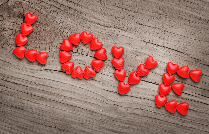 Word LOVE laid out from candy in heart shape on wooden background stock image
