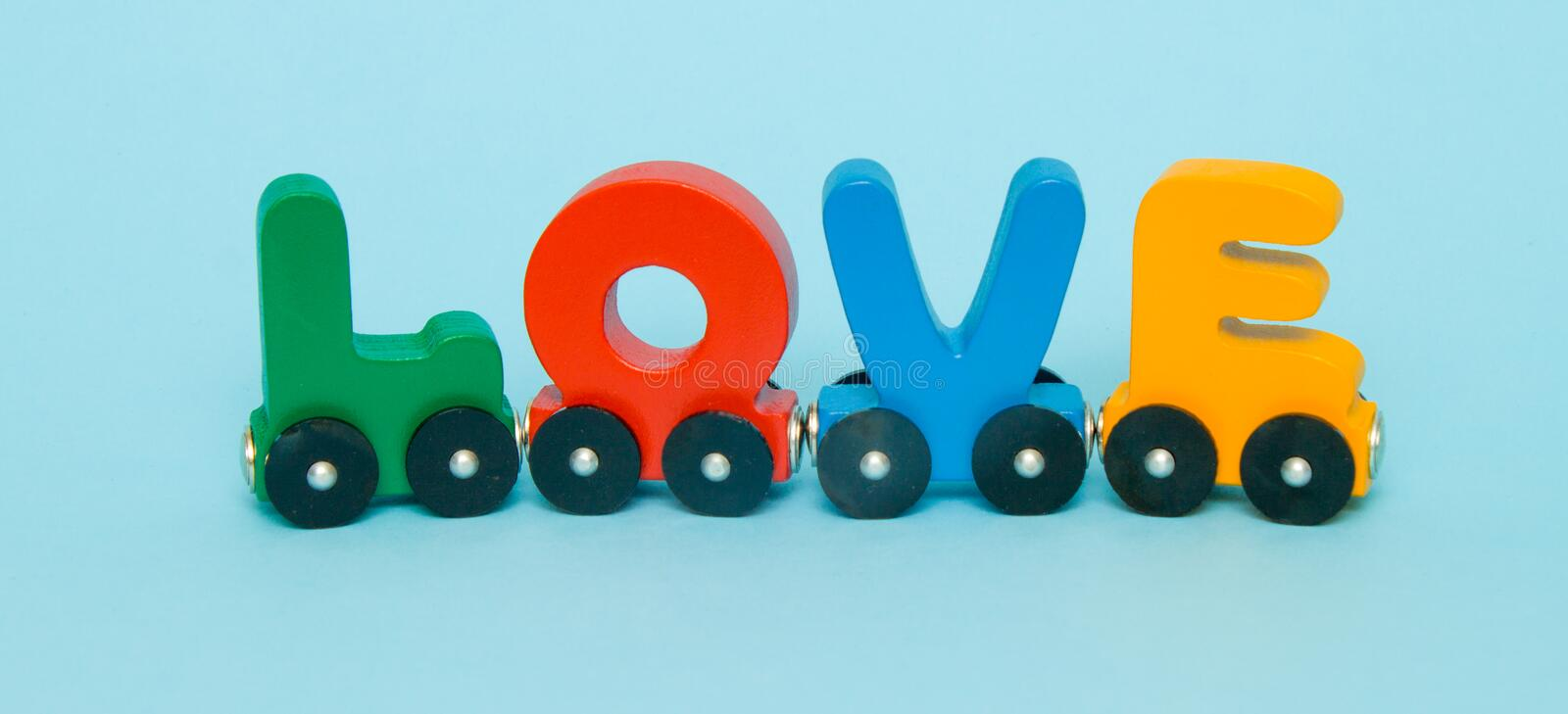 Word Love made of letters train alphabet. Bright colors of red yellow green and blue on a white background. Early childhood develo stock photo