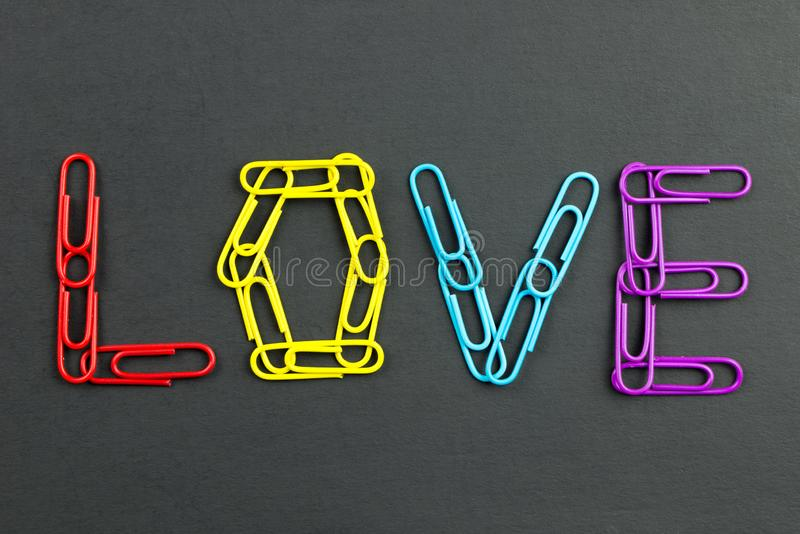 Word love made from paper clips. Word love made from colorful paper clips isolated on black background royalty free stock images