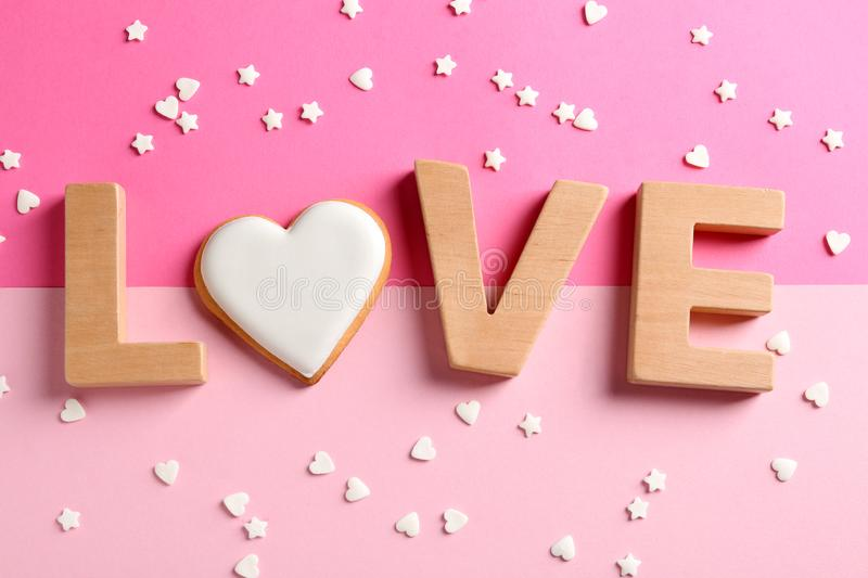 Word LOVE made with wooden letters and heart shaped cookie surrounded by candy confetti on color background royalty free stock image