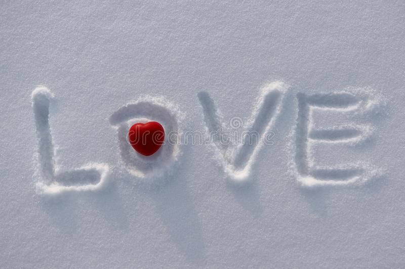 Word Love and red heart on snow royalty free stock photos