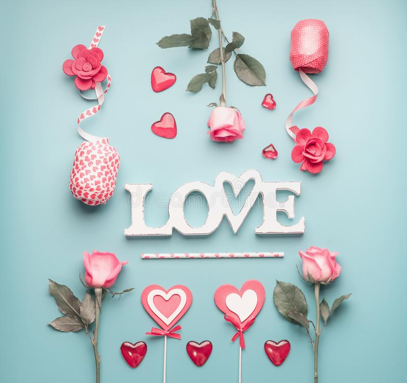 Word love with roses, hearts and decoration ribbons on pastel blue background, top view. Valentines day or abstract love concept royalty free stock image