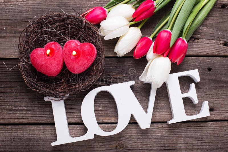 Word love, two red candles in form of heart in nest and bright stock images