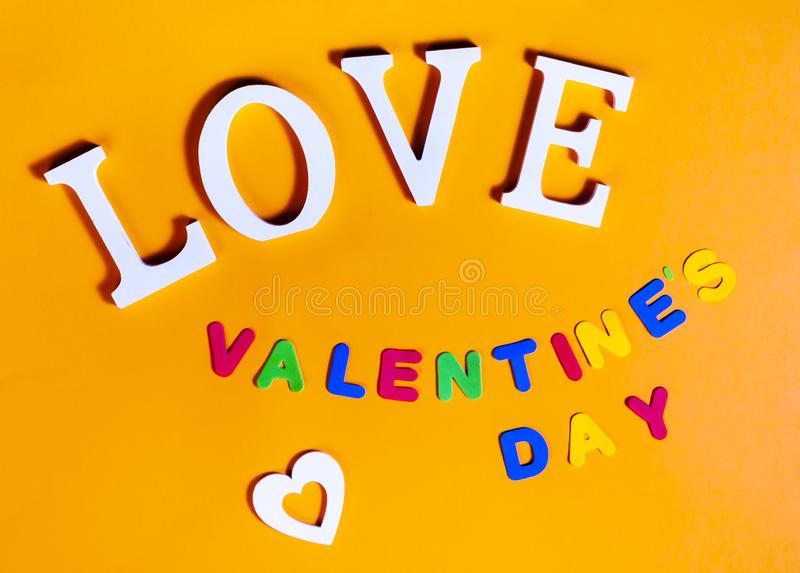 Word love in white, white heart and also colored words valentine`s day over orange background stock photos