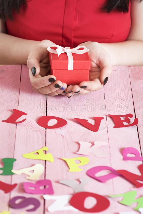 The word love and a woman holding a gift stock images
