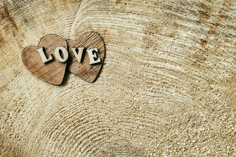 Word love from wooden letters on two wooden hearts, on wooden surface of saw cut, grunge texture , background royalty free stock photos