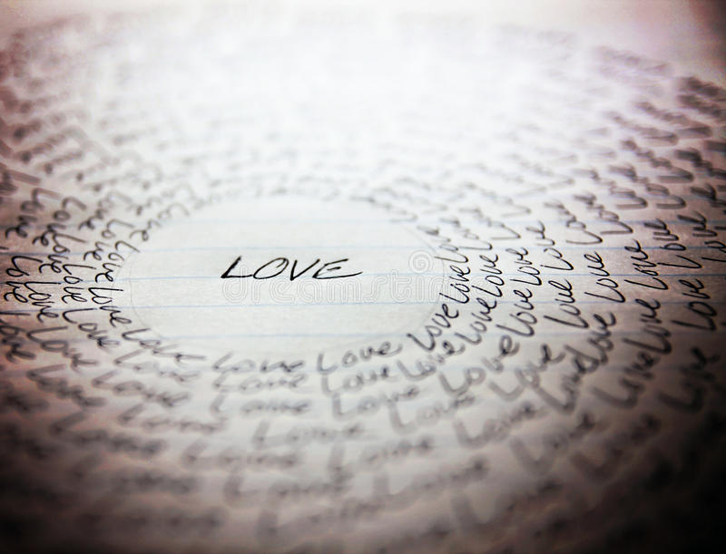 The word love written on a lined piece of school paper. In ink with a vignette and a circle of love (very shallowe depth of field - focus on the bottom of the stock photo