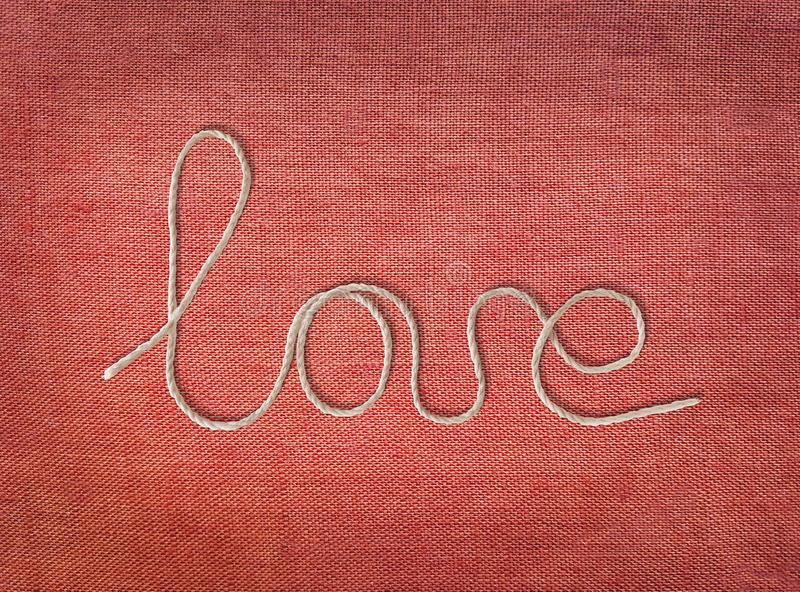 Word love written from rope on red canvas background. Text elements with shadow on pink cotton fabric texture. Close up, top view stock images