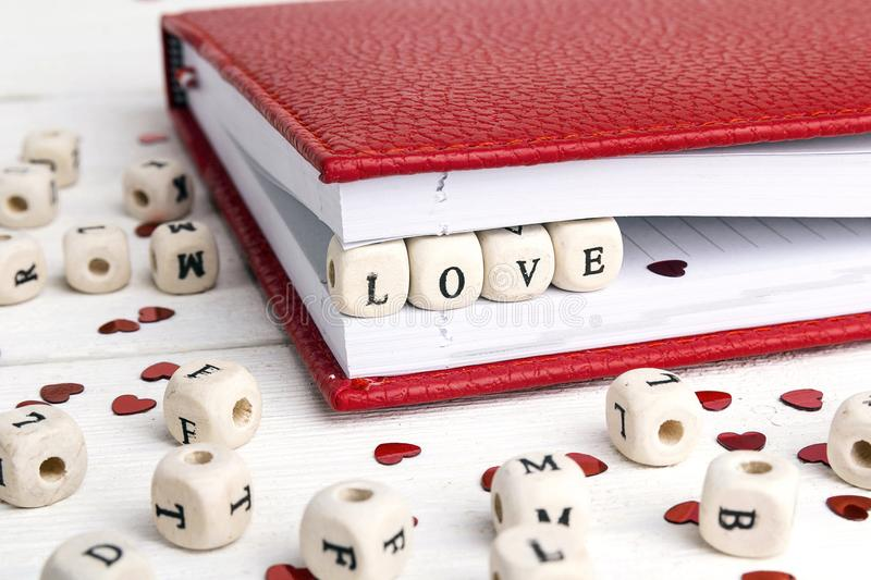 Word Love written in wooden blocks in a notebook on white wood royalty free stock photo
