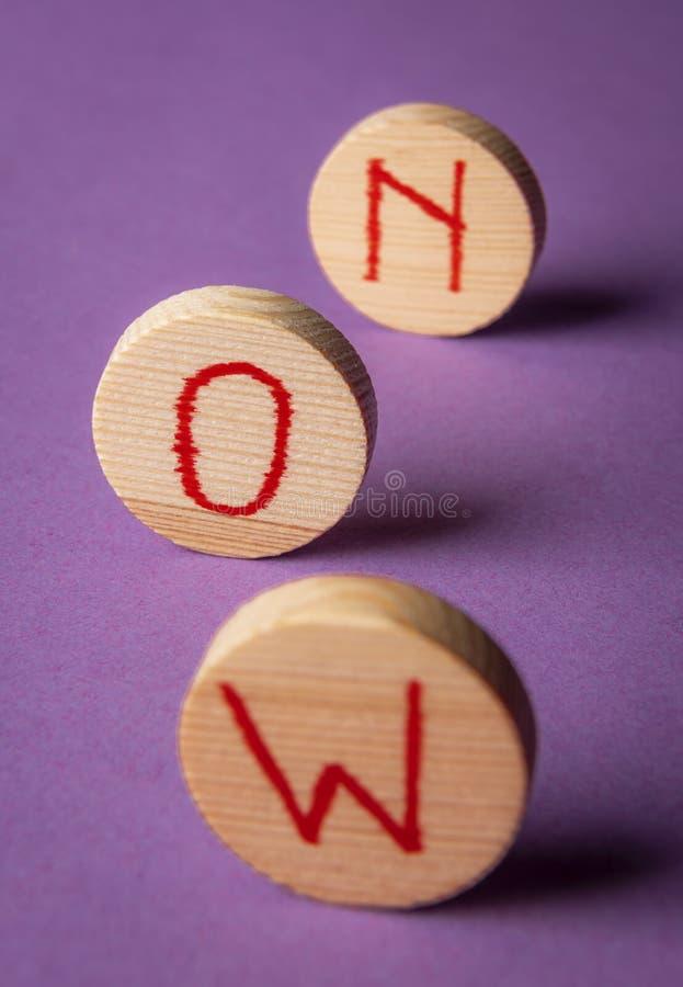 Word maintenant sur les morceaux en bois Saisissez le moment Fond pourpre images stock