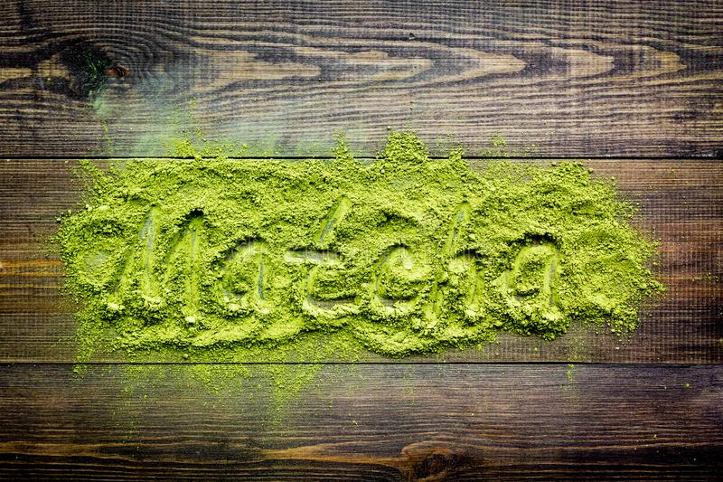 Word Matcha writed at matcha powder on dark wooden background top view stock image
