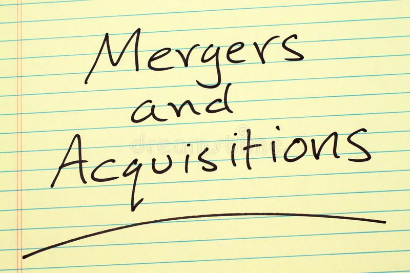 Mergers And Acquisitions On A Yellow Legal Pad royalty free stock photography