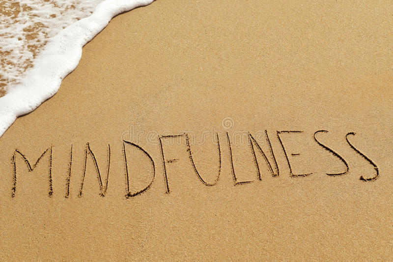 Word mindfulness in het zand stock fotografie