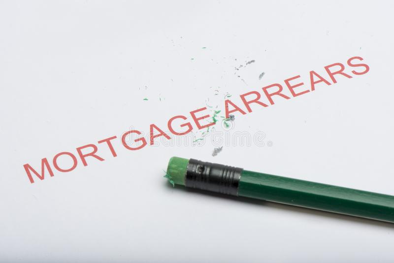 Word `Mortgage Arrears` with Worn Pencil Eraser and Shavings royalty free stock photography