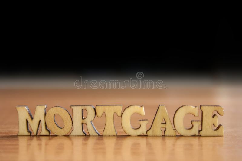 Word mortgage. The word & x27;mortgage& x27; made of wooden letters. wood inscription on table and dark black background royalty free stock photography
