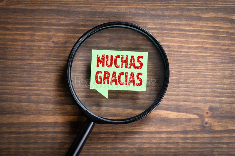 Word Muchas Gracias Means Thank You. Spanish language learning, search. Man`s hand, holding magnifying glass stock photo