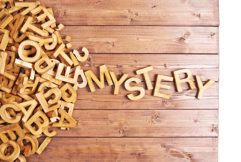 Word mystery made with wooden letters. Word mystery made with block wooden letters next to a pile of other letters over the wooden board surface composition stock photo