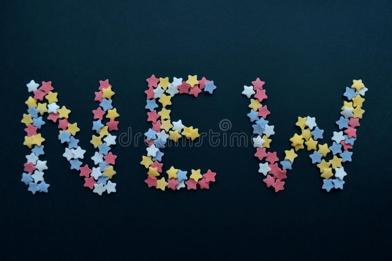 The word New in red white yellow and blue sugar stars, for business, advertising, commerce, sales stock images