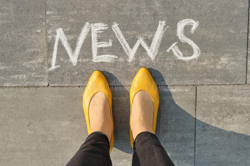Word news on gray sidewalk with women legs, top view.  stock photos