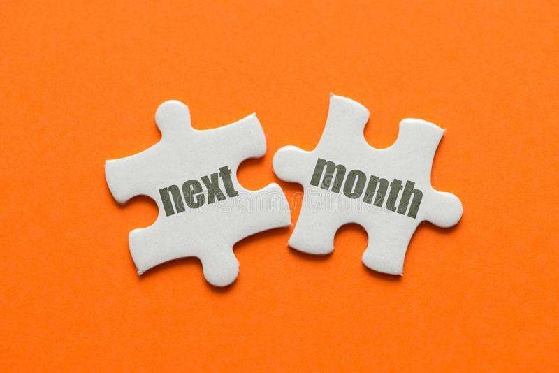 The word Next Month on two matching puzzle on orange background royalty free stock photo