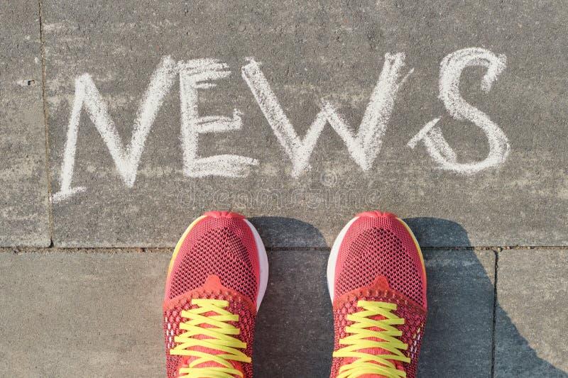 Word nieuws op grijze stoep met vrouwenbenen in tennisschoenen, hoogste mening stock fotografie