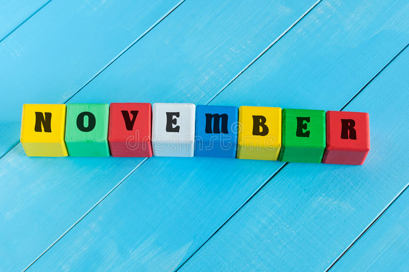 Word November on color wooden cubes with light. Blue wood background royalty free stock photos