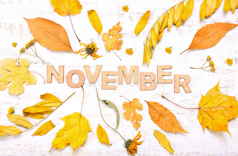 The word. `november` with yellow leaves on a white wooden background. Autumn composition royalty free stock photo