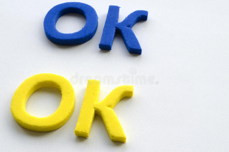 The Word Okay Which Is Written By Blue And Yellow Letters Stock
