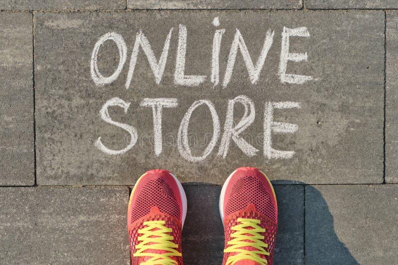 Word online opslag die op grijze stoep met vrouwenbenen wordt geschreven in tennisschoenen, hoogste mening royalty-vrije stock fotografie