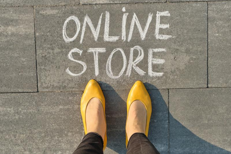 Word online store written on gray sidewalk with women legs, top view.  stock images