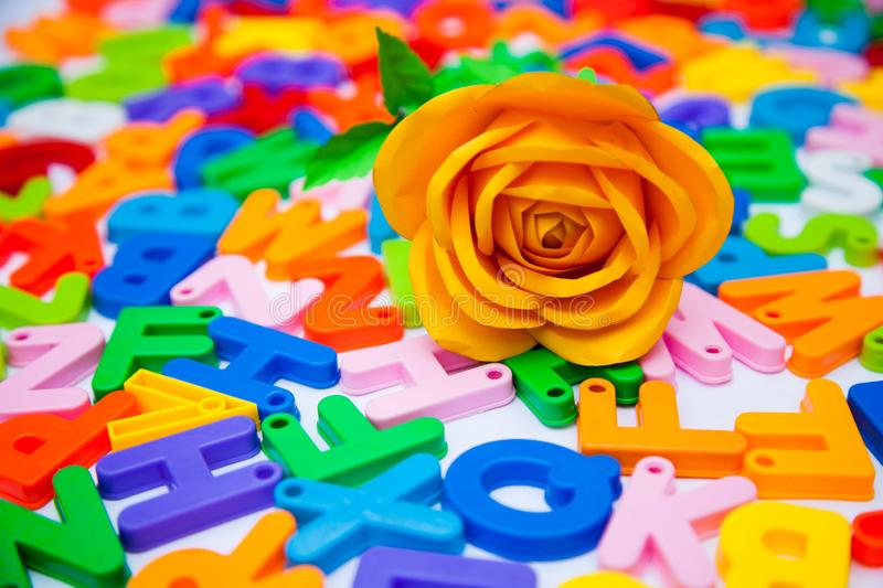 A paper rose placed on colorful alphabet blocks stock images