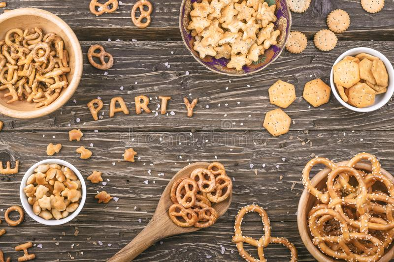 Word party written with crackers letters on wooden background. S stock photos